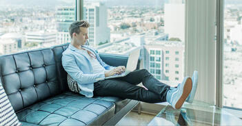 well-dressed man sitting by a window in a high rise apartment