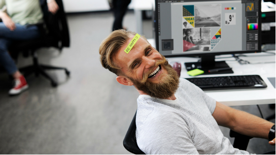 Man in an office smiling with a Post-It Note stuck on his forehead