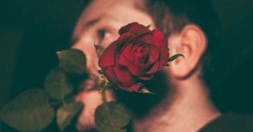 man holding rose in his teeth