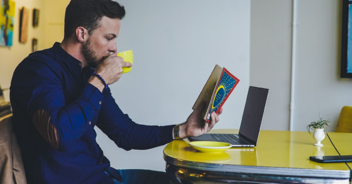 image of man reading a book and drinking coffee