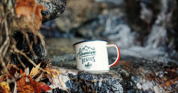 photo of mug sitting on rocks with text that says adventure begins