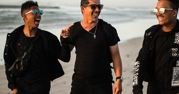 Image of three men walking on the beach together and laughing