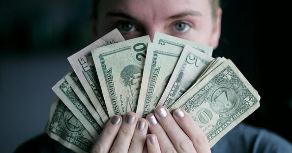 Person holding money up, fanned out in front of his face