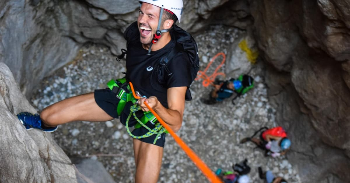 Man rock climbing who is looking up and winking at the camera