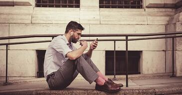photo of man sitting on the sidewalk and looking at his phone