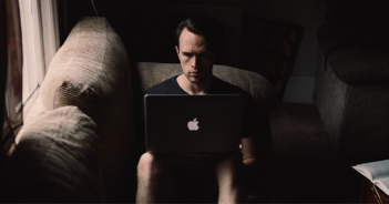 Image of man sitting on a sofa with a MacBook in his lap