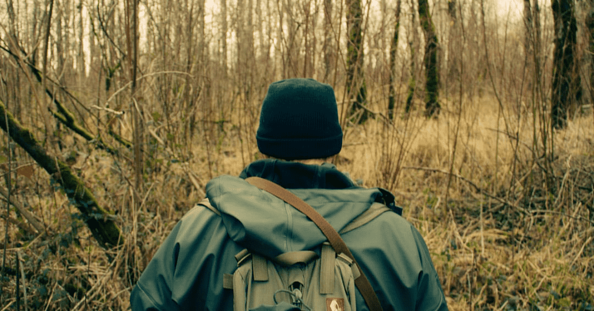 Speed of Progress Featured Image   Description: person with back toward camera walking in the woods