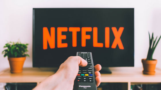 Photo of person pointing a tv remote at a television displaying the netflix logo