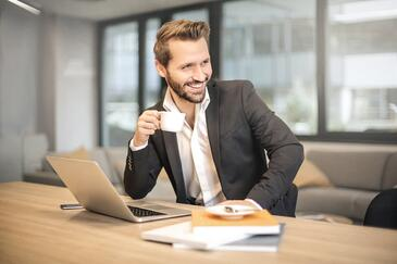 bearded man smiling and holding a cup of coffee