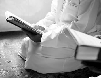 muslim man kneeling and reading the Quran