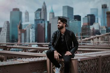 man in black leather jacket sitting on a ledge with a city skyline in the background