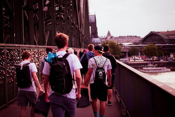 young men wearing backpacks walking across a bridge