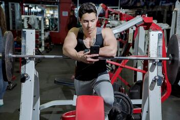 man on cell phone leaning against barbell