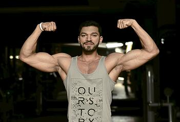 muscular man in a tank top flexing his biceps