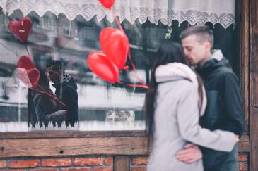heterosexual couple kissing outside a shop