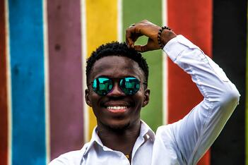 man smiling in front of a colorful wall