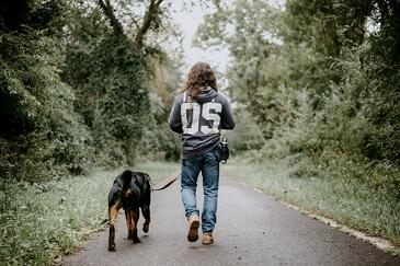 Man with long hair walking his dog