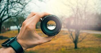 Struggling to focus– photo of a person holding a camera lens in front of a landscape background