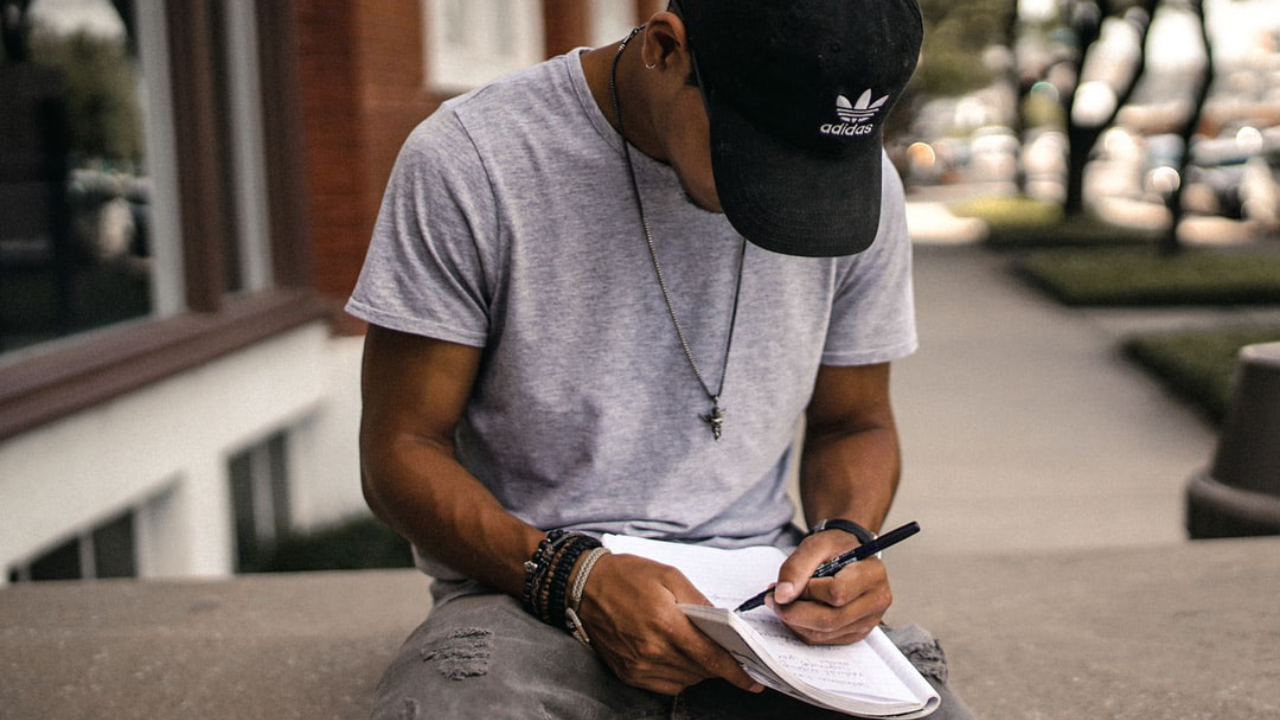 man sitting outside writing in a notebook