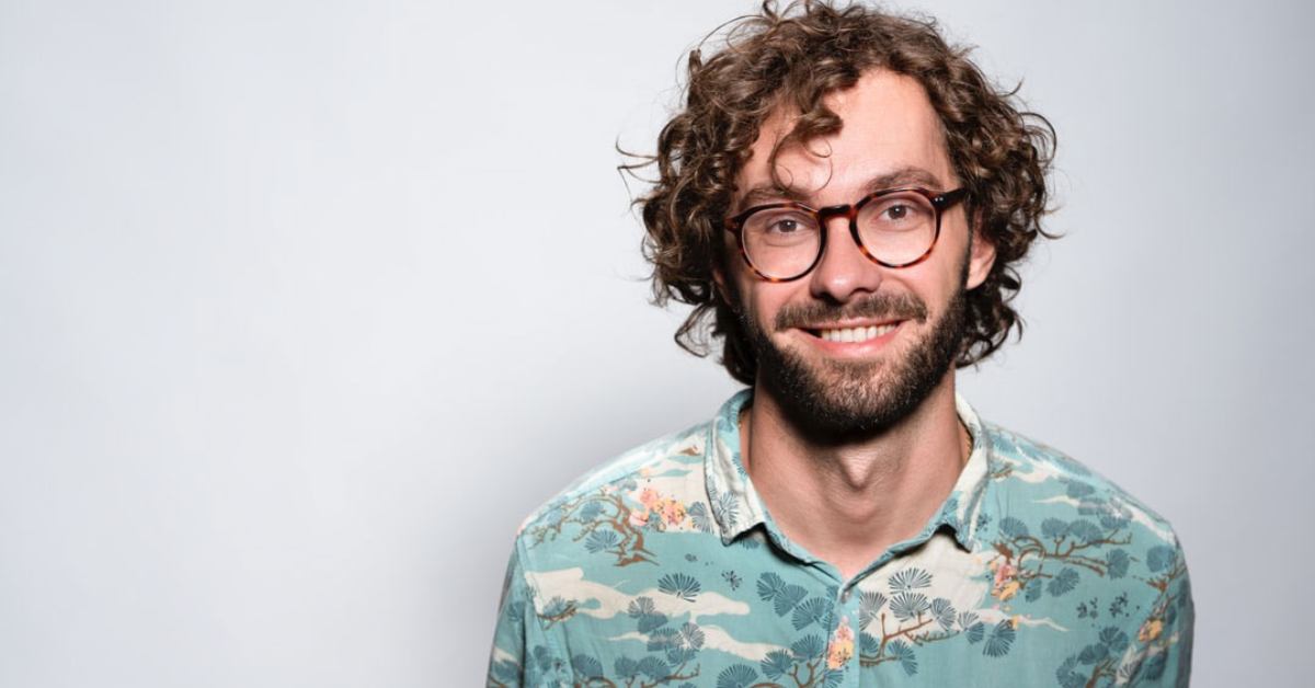 man smiling in a floral shirt