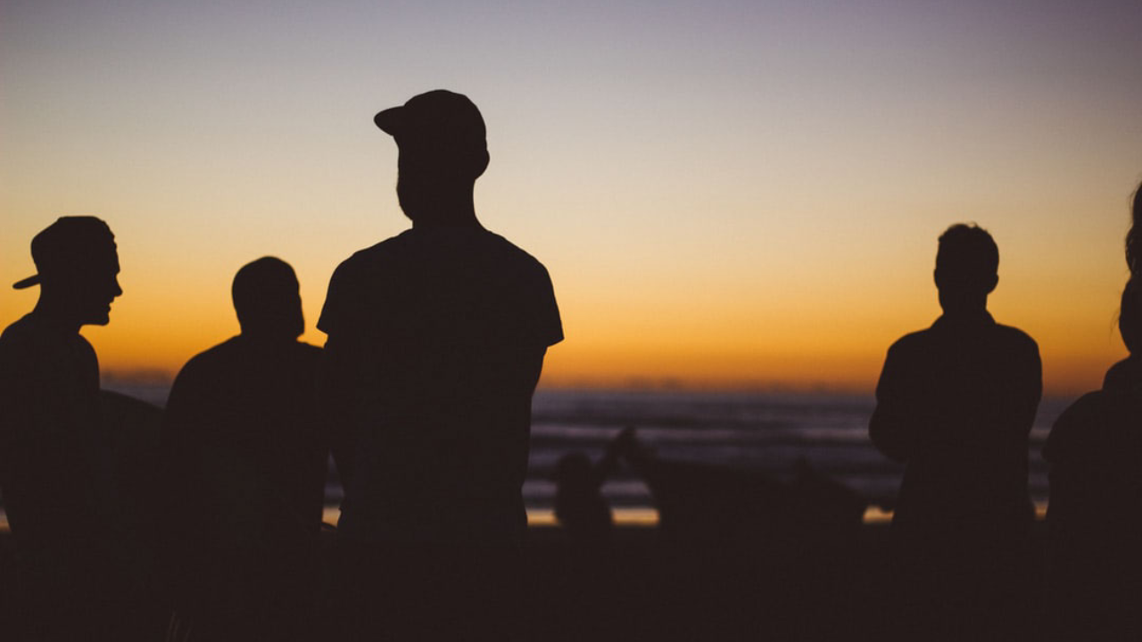 silhouette of men against a sunset