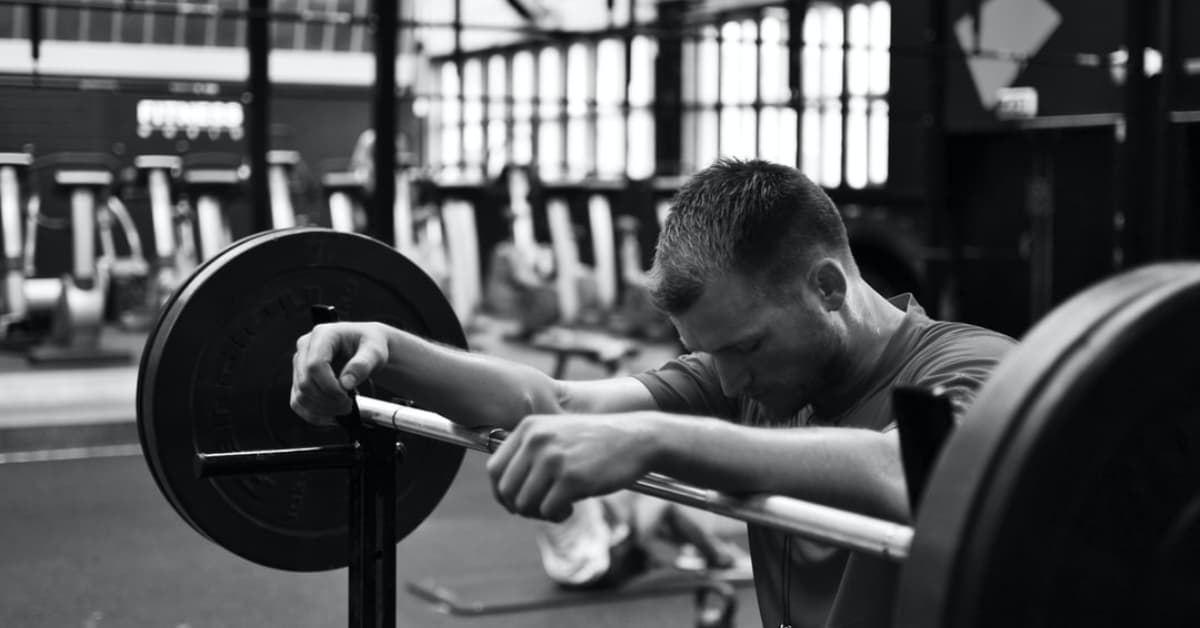 Black and white photo of man leaning against a barbell