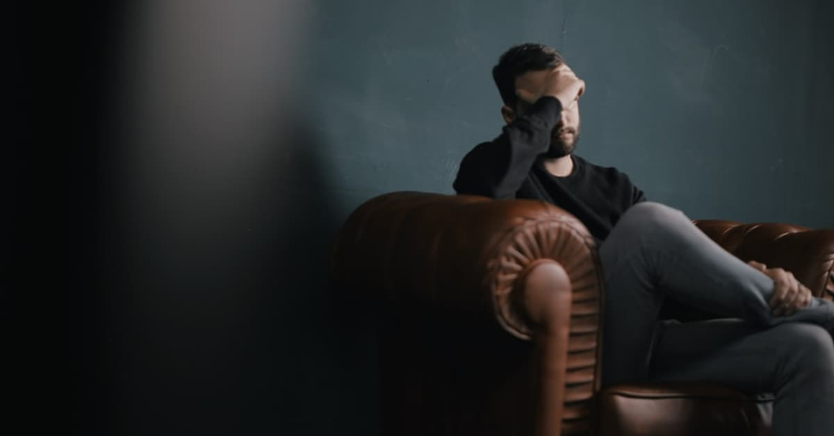 Man sitting on a recliner in a dark room with his hand on his face