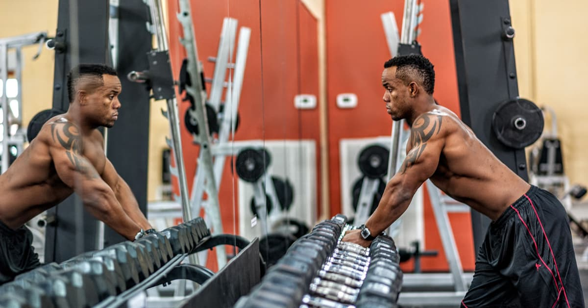 muscular black man leaning over a dumbbell rack