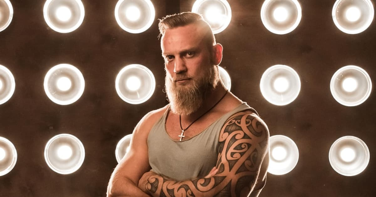 Photo of tattooed, muscular man standing with his arms crossed