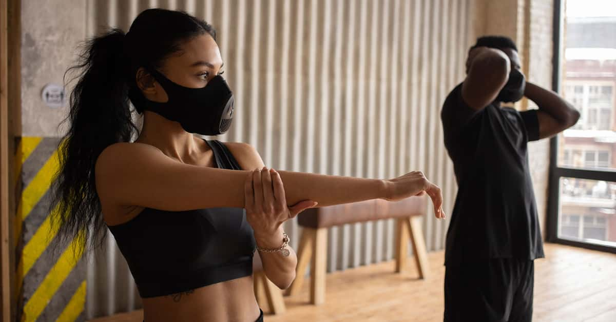 two people working out while wearing masks and social distancing