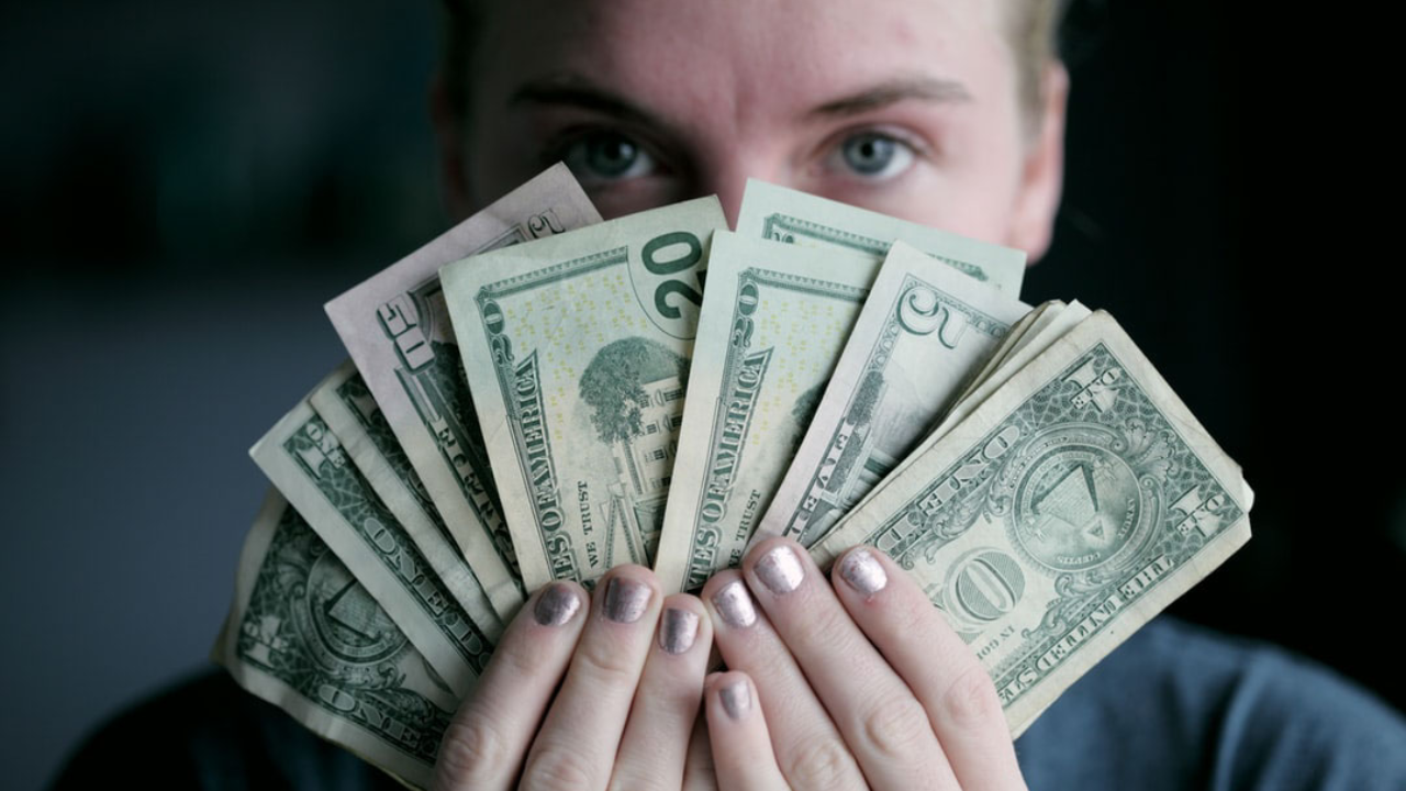 realistic ways to make more money featured image– person holding currency